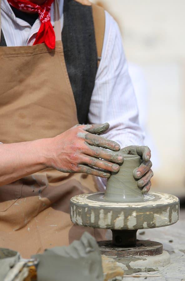 Traînez avec le tour de main pendant la production d'un pot avec de l'argile photographie stock