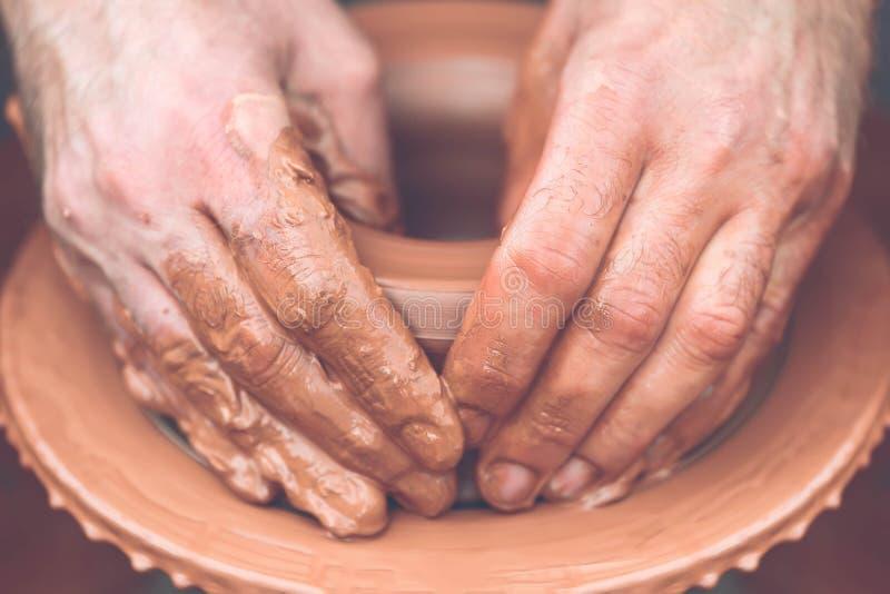 traînez en faisant le pot en céramique sur la roue de poterie photographie stock libre de droits