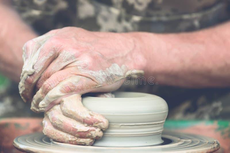 traînez en faisant le pot en céramique sur la roue de poterie image libre de droits