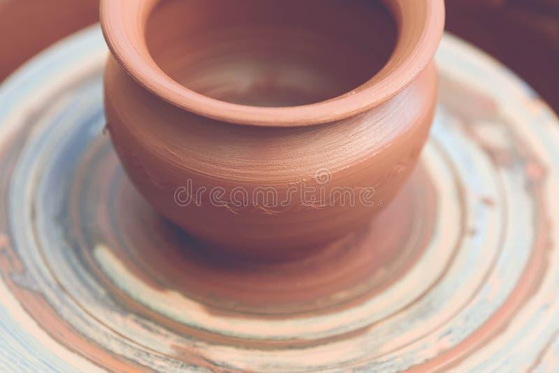 traînez en faisant le pot en céramique sur la roue de poterie image stock