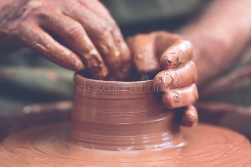 traînez en faisant le pot en céramique sur la roue de poterie photographie stock