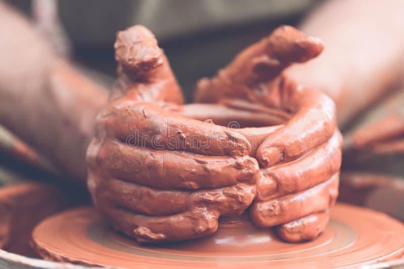 traînez en faisant le pot en céramique sur la roue de poterie photos stock