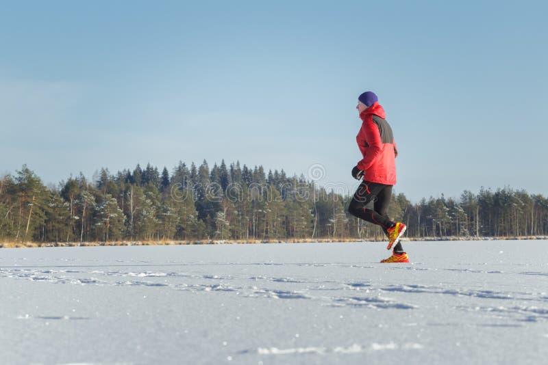 Traînez l'homme de coureur dans la course de sport d'hiver extérieure photographie stock libre de droits