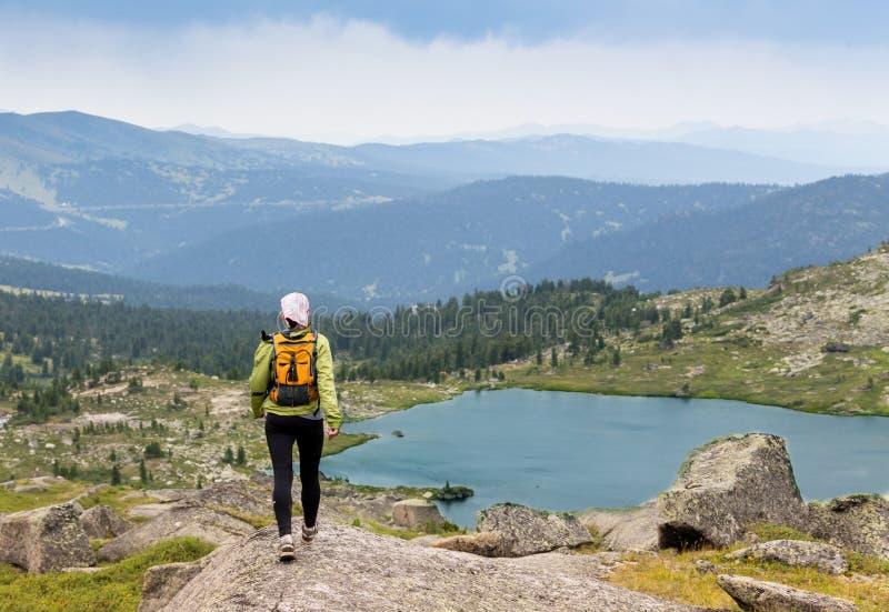Traînez le pays croisé de femme courante en montagnes le beau jour d'été images stock