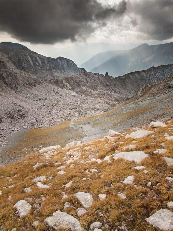 Traînez par le paysage de haute montagne avec les nuages et le soleil de tempête photographie stock