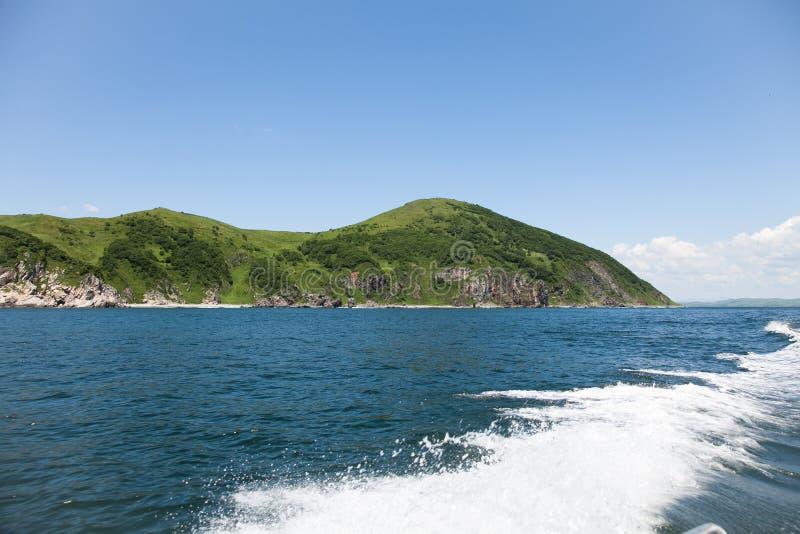 Traînez sur la surface d'eau de mer derrière le bateau contre le contexte du terrain accidenté photos stock