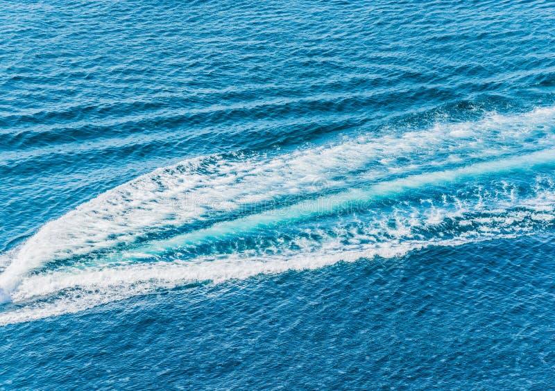 Traînez sur la surface de l'eau derrière du canot automobile rapide images libres de droits