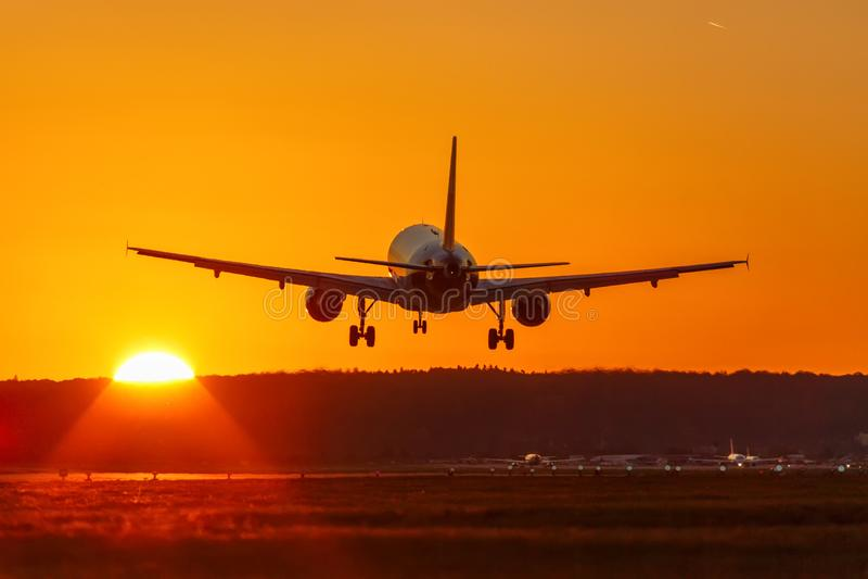 Tra праздников каникул захода солнца солнца авиапорта летания посадки самолета стоковое изображение rf