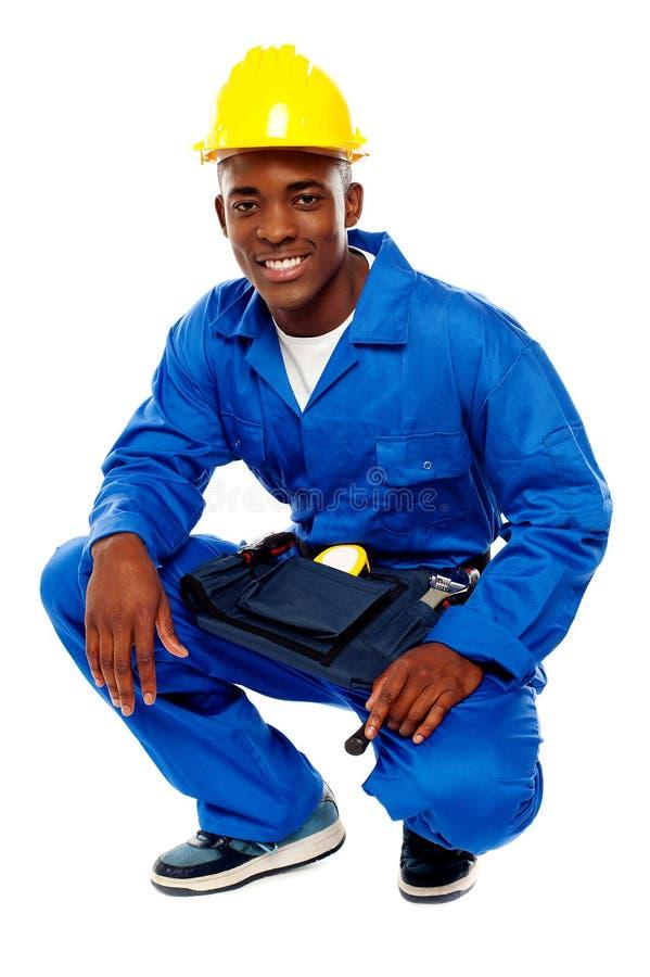 Trabajador africano asentado que presenta con una sonrisa foto de archivo libre de regalías