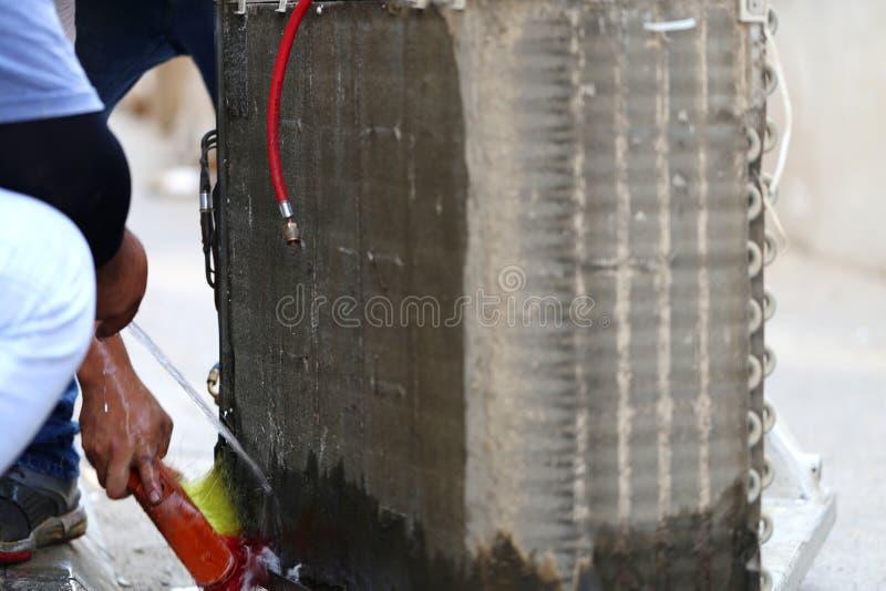 Trabajador al refrigerador de limpieza de la bobina del acondicionador de aire por el agua para limpio un polvo en la pared en ho fotografía de archivo libre de regalías