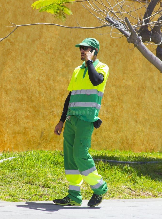 Trabajador ambiental del consejo local del Los Cristianos Tenerife A que lleva la ropa protectora de la alta visibilidad completa imagen de archivo libre de regalías