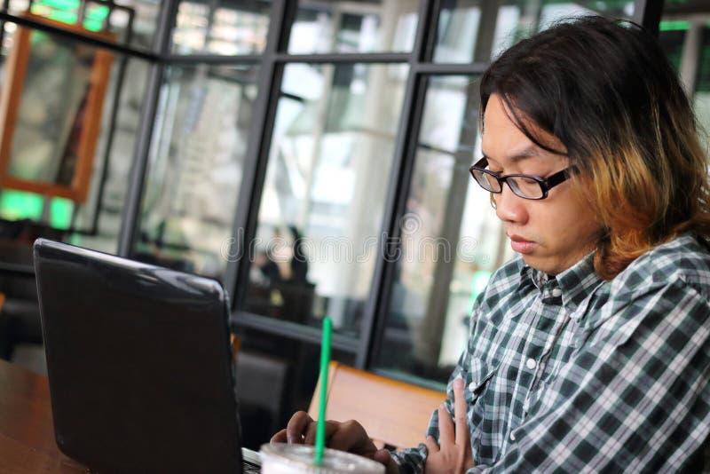 Trabajador asiático joven perezoso que usa el ordenador portátil en lugar de trabajo de la oficina moderna fotografía de archivo