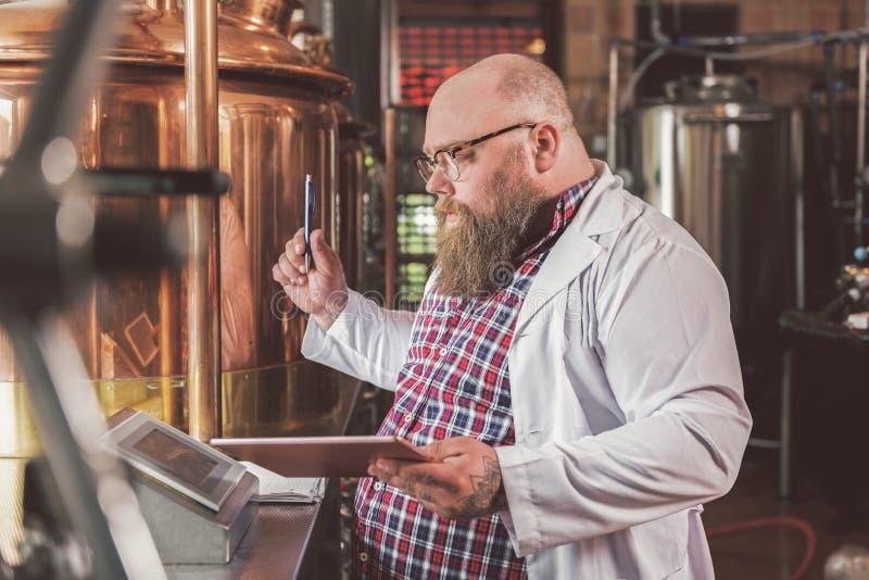 Trabajador barbudo agradable que hace la cerveza foto de archivo