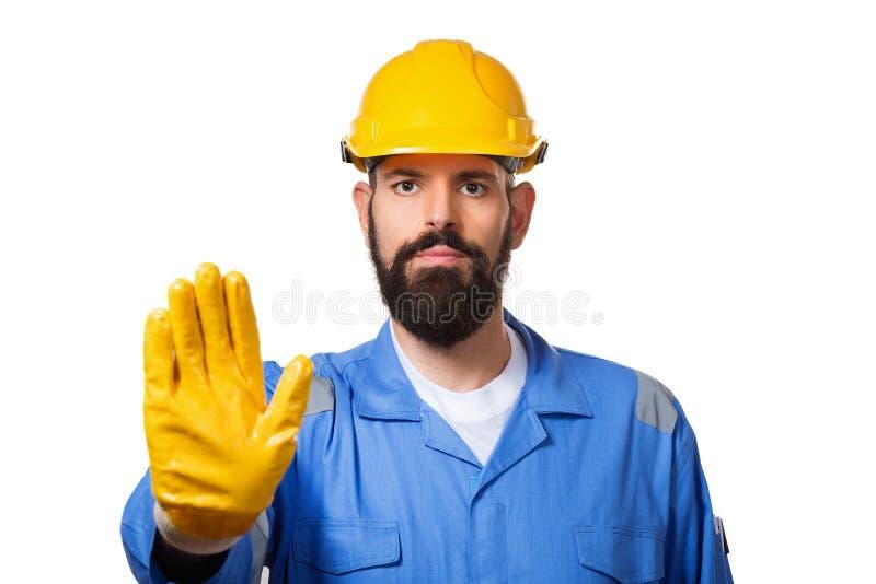 Trabajador barbudo de la Edad Media con el casco amarillo y uniforme que hace gesto de la parada con su mano que niega una situac imágenes de archivo libres de regalías
