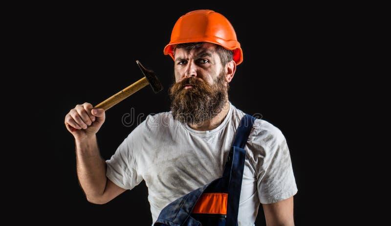 Trabajador barbudo del hombre con la barba, casco del edificio, casco Martilleo del martillo Constructor en el casco, martillo, m imagenes de archivo