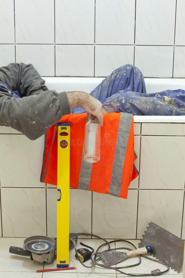 Trabajador borracho que duerme en el baño imagen de archivo libre de regalías