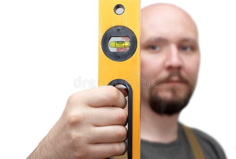 Trabajador calvo con el nivel amarillo fotos de archivo