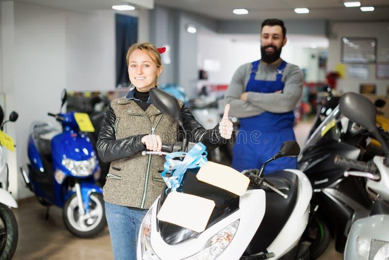 Trabajador con el cliente de la mujer en lugar de trabajo de la motocicleta foto de archivo