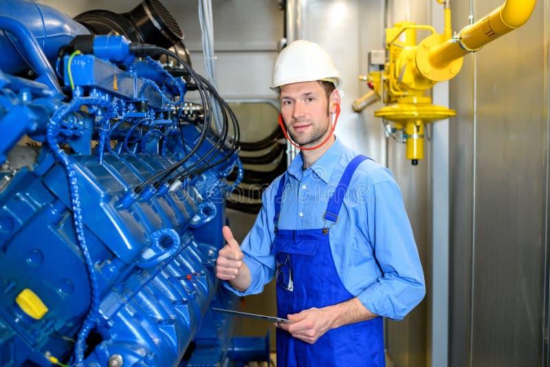 Trabajador con el funcionamiento del casco en el pulgar grande de la demostración del generador para arriba imagen de archivo libre de regalías