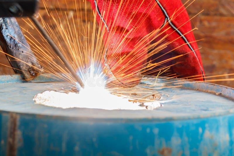 Trabajador con el guante rojo para proteger la luz de la chispa con proceso de soldadura con el metal azul del tubo y el acero br fotos de archivo libres de regalías