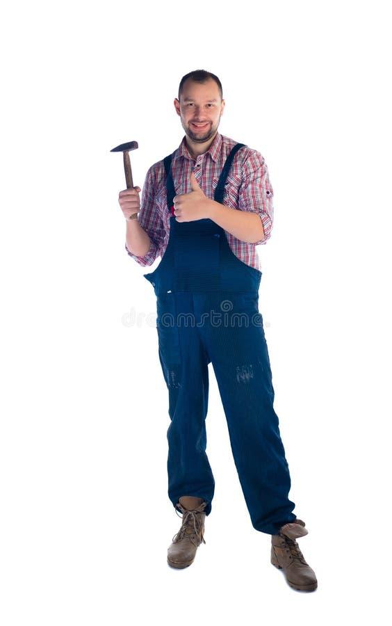 Trabajador con el martillo que se coloca en el fondo blanco imagen de archivo