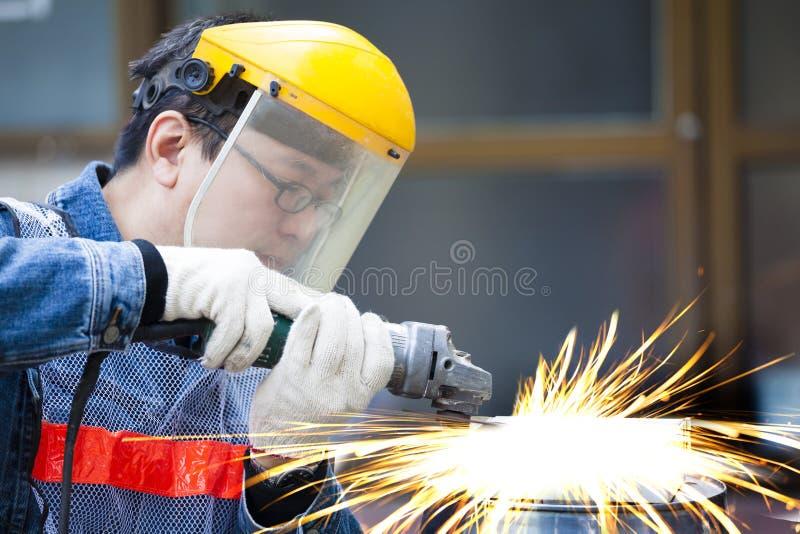 Trabajador con el metal del corte de máquina de la amoladora imagen de archivo