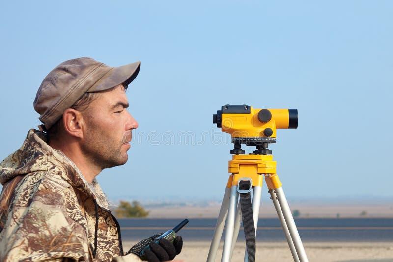 Trabajador con el nivel, constructor del topógrafo con el equipo de la geodesia cerca de la carretera, con el teléfono móvil, son fotografía de archivo
