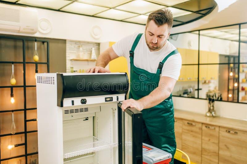 Trabajador con el refrigerador de la reparación de la caja de herramientas en casa imágenes de archivo libres de regalías