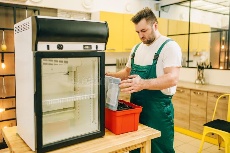 Trabajador con el refrigerador de la reparaci?n de la caja de herramientas en casa imagenes de archivo