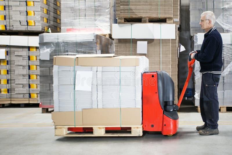 Trabajador con Handtruck cargado en Warehouse imagen de archivo libre de regalías