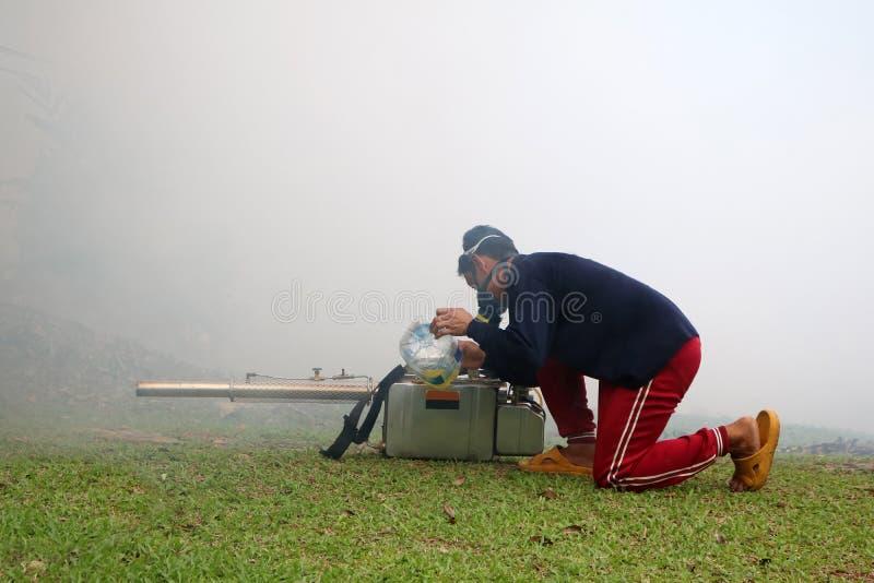 Trabajador con humo y máquina el empañarse en el jardín fotos de archivo