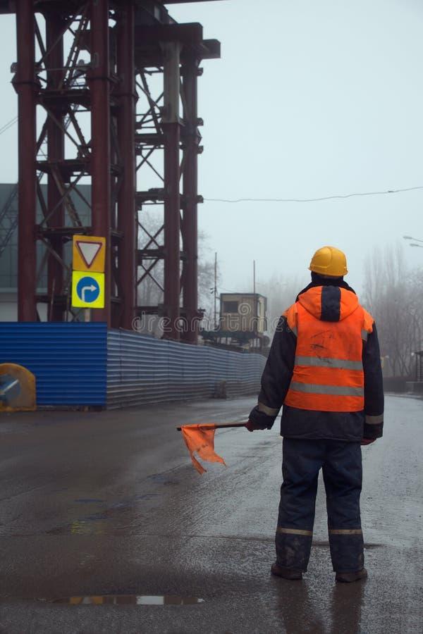 Trabajador con la bandera que se coloca a través del camino que previene tráfico en área de la construcción foto de archivo