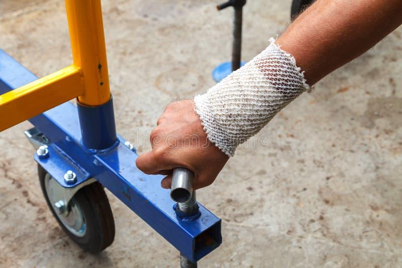 Trabajador con la mano vendada en el trabajo fotografía de archivo libre de regalías