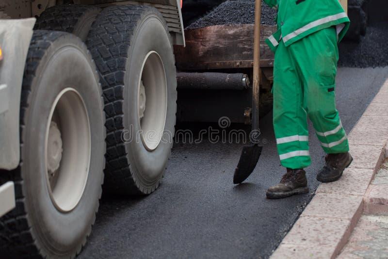 Trabajador con la pala que trabaja en el nuevo asfalto imagen de archivo