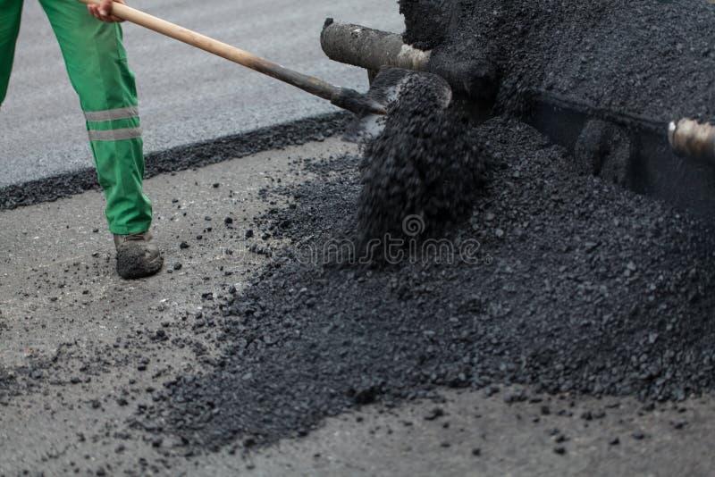 Trabajador con la pala que trabaja en el nuevo asfalto foto de archivo