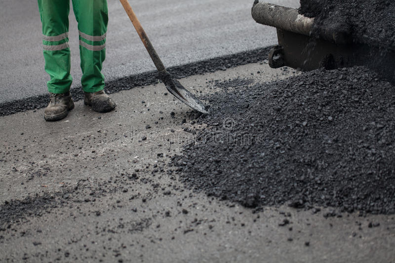 Trabajador con la pala que trabaja en el nuevo asfalto fotos de archivo