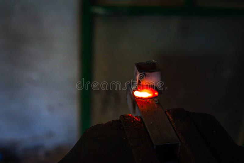 Trabajador con la pieza de metal de soldadura de los guantes protectores en taller foto de archivo