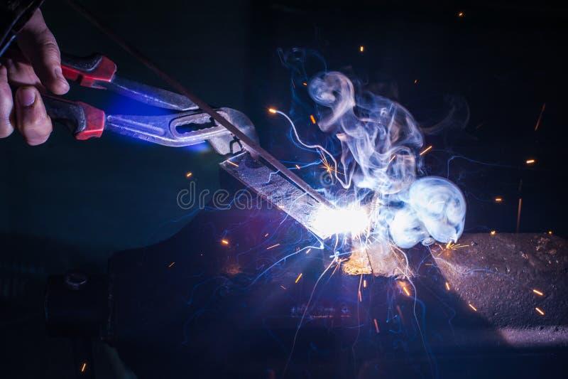Trabajador con la pieza de metal de soldadura de los guantes protectores en taller imagen de archivo