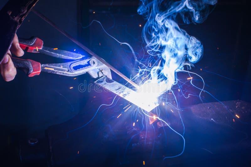 Trabajador con la pieza de metal de soldadura de los guantes protectores en taller foto de archivo libre de regalías