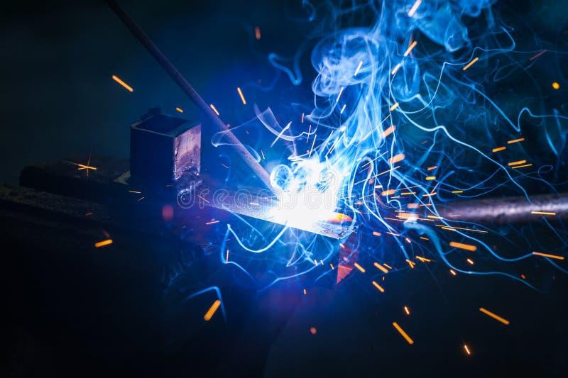 Trabajador con la pieza de metal de soldadura de los guantes protectores en taller fotografía de archivo