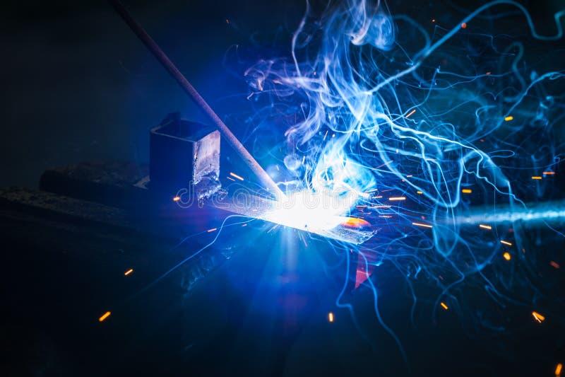 Trabajador con la pieza de metal de soldadura de los guantes protectores en taller imagen de archivo libre de regalías