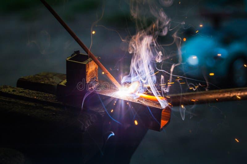 Trabajador con la pieza de metal de soldadura de los guantes protectores en taller imágenes de archivo libres de regalías