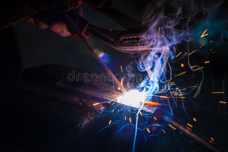 Trabajador con la pieza de metal de soldadura de los guantes protectores en taller imagenes de archivo