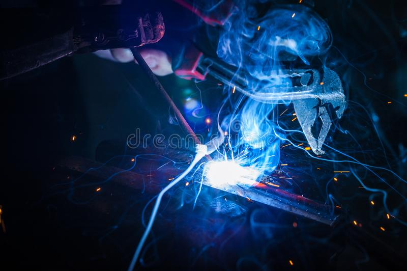 Trabajador con la pieza de metal de soldadura de los guantes protectores en taller fotos de archivo