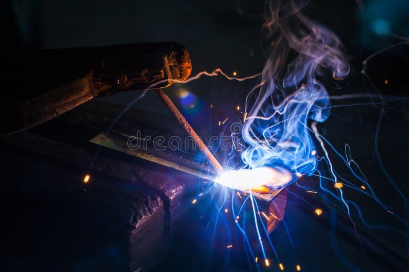 Trabajador con la pieza de metal de soldadura de los guantes protectores en taller fotos de archivo libres de regalías