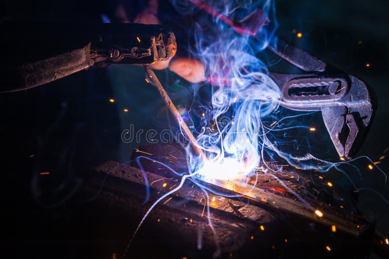 Trabajador con la pieza de metal de soldadura de los guantes protectores en taller fotografía de archivo libre de regalías