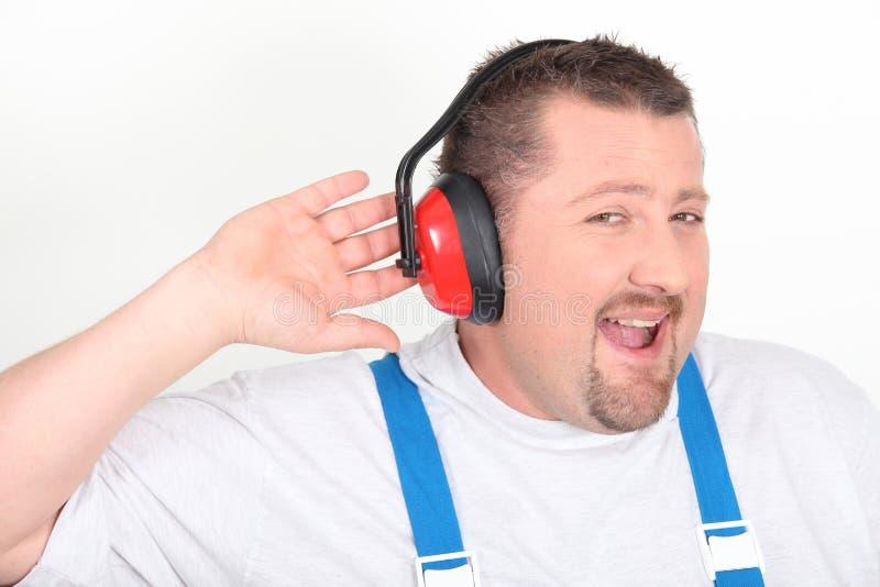 Trabajador con los auriculares de ruido-cancelación fotos de archivo