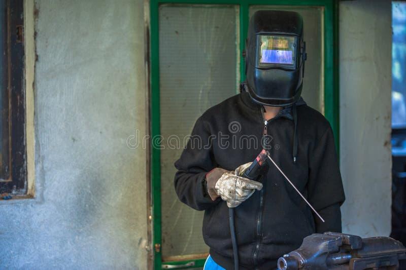 Trabajador con los guantes protectores y pieza de metal de soldadura de la máscara protectora en taller foto de archivo libre de regalías