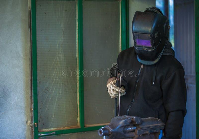 Trabajador con los guantes protectores y pieza de metal de soldadura de la máscara protectora en taller imagenes de archivo