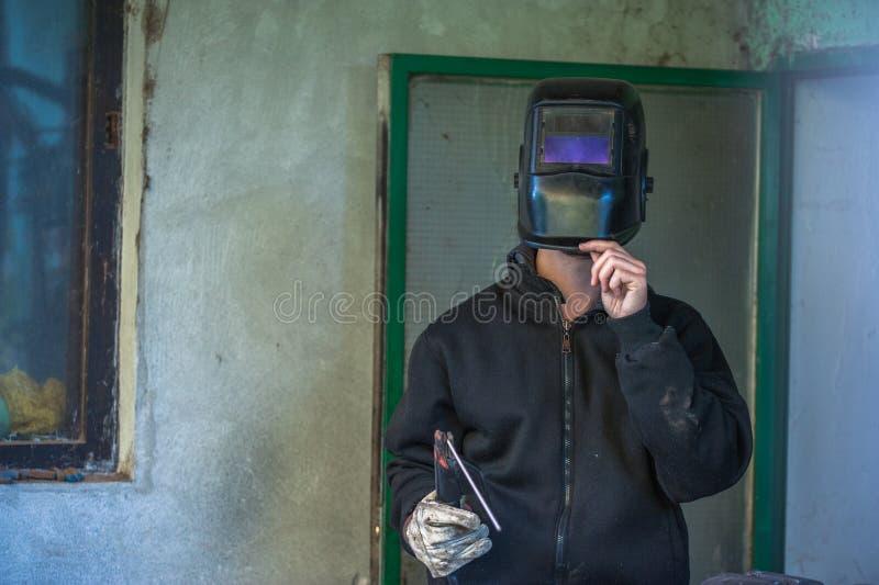 Trabajador con los guantes protectores y pieza de metal de soldadura de la máscara protectora en taller imagen de archivo
